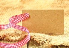 与一条新鲜的土气丝带的空白的棕色标记 库存照片