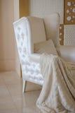 与一条毯子的白色椅子在演播室 库存照片