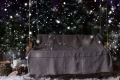 与一条毯子的空的木摇摆在一个积雪的公园或fo 图库摄影