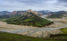 与一条流动的河的高五颜六色的山土坎从Blahnakur山, Landmannalaugar,冰岛山顶的谷视图的  图库摄影
