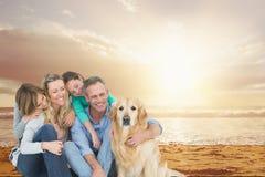 与一条狗的微笑的家庭在海滩 免版税库存照片