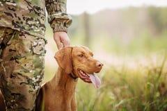 与一条狗的猎人在森林 免版税库存照片