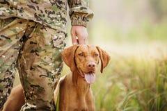 与一条狗的猎人在森林 图库摄影