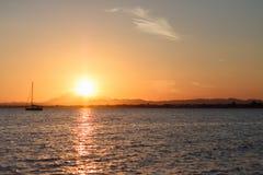 与一条现出轮廓的小船的日落 免版税图库摄影
