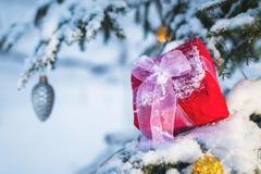 与一条白色丝带的特写镜头红色新年的礼物在一棵积雪的圣诞树的分支的圣诞节玩具旁边 库存照片
