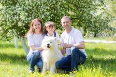 与一条白色狗的愉快的家庭在夏天公园 免版税库存图片