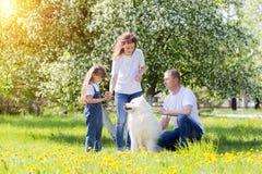 与一条白色狗的愉快的家庭在夏天公园 免版税库存照片