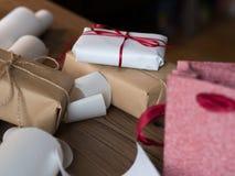 与一条红色丝带的一件礼物和几个其他礼物和袋子 库存照片