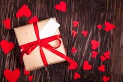 与一条红色丝带的土气礼物在木背景 免版税图库摄影