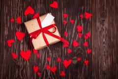 与一条红色丝带的土气礼物在木背景 免版税库存图片