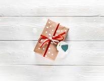 与一条红色丝带的圣诞节礼物在与雪花的白色背景 图库摄影