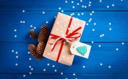 与一条红色丝带的圣诞节礼物在与雪花的蓝色背景 免版税图库摄影