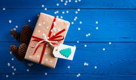 与一条红色丝带的圣诞节礼物在与雪花的蓝色背景 免版税库存照片