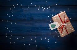 与一条红色丝带的圣诞节礼物在与雪花的蓝色背景 库存照片