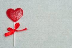 与一条红色丝带的心脏形状棒棒糖被栓对棍子零件 库存照片