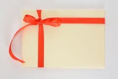 与一条红色丝带的淡黄色信封在白色背景 图库摄影
