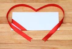 与一条红色丝带的白色信封在木桌上 免版税库存照片