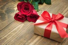 与一条红色丝带的礼物和玫瑰花束在您的生日或华伦泰` s天充满爱对一名妇女木背景的 C 库存照片