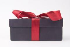 与一条红色弓和丝带的礼物盒 库存照片
