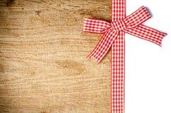 与一条红色方格的丝带的木背景 库存图片