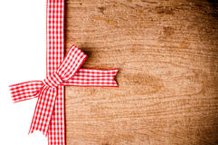与一条红色方格的丝带的木背景 免版税图库摄影
