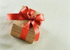 与一条红色缎丝带和弓的棕色礼品 免版税库存照片