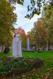 与一条红色领巾的一个雕象在Zrinjevac公园在秋天,萨格勒布,克罗地亚 库存照片