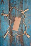 与一条绳索的晒衣夹在蓝色木板 图库摄影