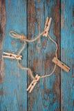 与一条绳索的晒衣夹在蓝色木板 免版税库存照片