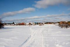 与一条路的冬天农村风景在村庄 图库摄影