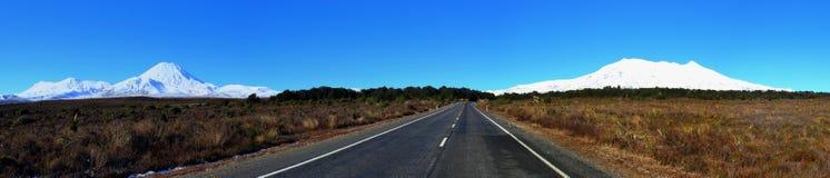 与一条路的Panoramatic Ngauruhoe和Ruapehu火山在中部 免版税图库摄影
