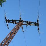 与一条输电线的老生锈的帆柱在蓝天上前面  免版税库存照片
