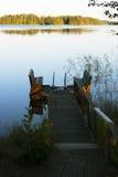 与一条长凳的空的人行桥在日出的一个湖 免版税库存照片