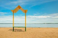 与一条长凳的空的海滩与在海岸的一个机盖 库存照片