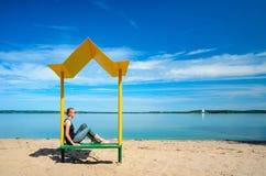 与一条长凳的空的海滩与在海岸的一个机盖 免版税库存照片