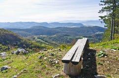 与一条长凳的观点在登上Bobija,周围的峰顶、小山、草甸和五颜六色的森林美丽的景色  库存图片
