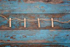 与一条绳索的晒衣夹在蓝色木板 库存图片