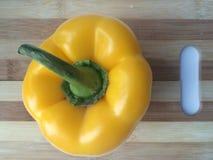 与一条绿色尾巴的黄色胡椒在切板 图库摄影