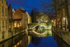 与一条绿色运河的都市风景在布鲁日在晚上 免版税库存照片