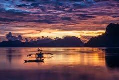 与一条banca小船的热带五颜六色的日落在El Nido 免版税图库摄影