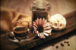 与一杯咖啡的可爱的构成和咖啡豆和花 图库摄影