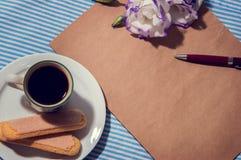 与一杯咖啡的平的位置桌、笔记本、笔和花,被过滤和被定调子的葡萄酒 免版税库存照片