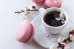 与一杯咖啡的桃红色蛋白杏仁饼干和白花分支  免版税库存图片