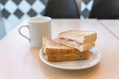 与一杯咖啡的火腿和乳酪三明治早餐 库存图片