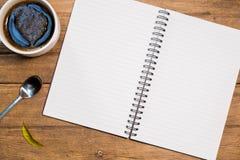 与一杯咖啡的笔记本在木桌上的 顶视图 库存图片