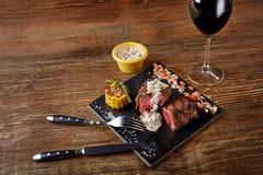 与一杯的烤肉牛排作为特写镜头的红葡萄酒在木背景的黑人委员会 库存照片
