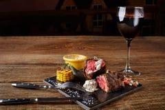 与一杯的烤肉牛排作为特写镜头的红葡萄酒在木背景的黑人委员会 免版税库存照片