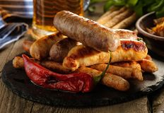 与一杯的烤香肠在一张木桌上的啤酒 土气 图库摄影