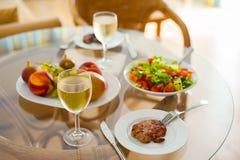 与一杯的自然健康食物午餐在一张透明桌上的酒 库存照片