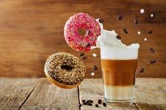 与一杯的飞行的多彩多姿的油炸圈饼咖啡 图库摄影